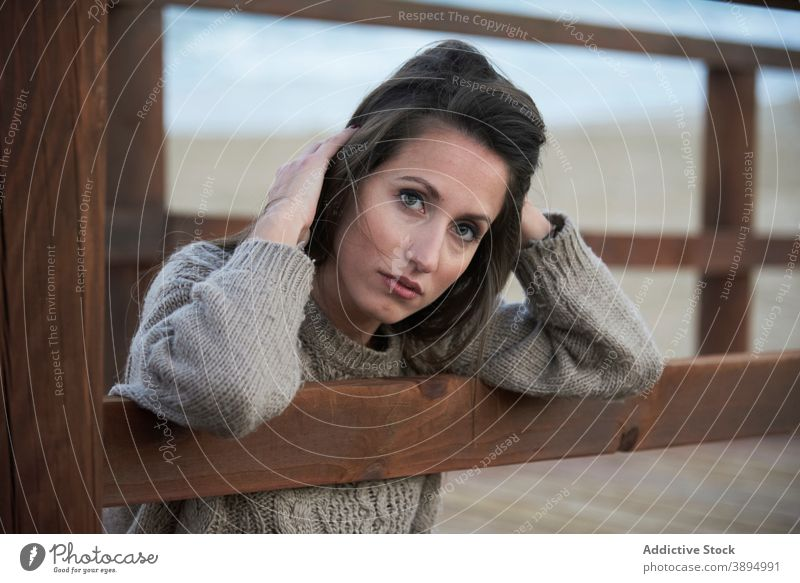 Tender woman on boardwalk on beach sweater fence promenade calm serene alone beautiful recreation lean on casual rest tranquil style charming leisure female