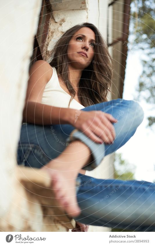 Casual woman in denim on windowsill casual chill barefoot calm serene thoughtful exterior building house facade dream alone serious jeans brunette summer
