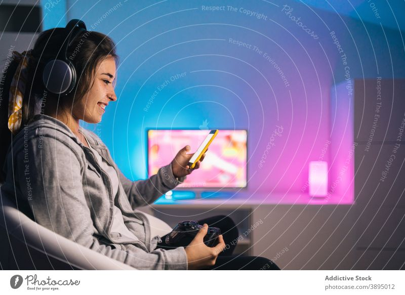 Smiling female gamer using smartphone at home woman gamepad controller console browsing joystick videogame cheerful evening smile headphones entertain sit