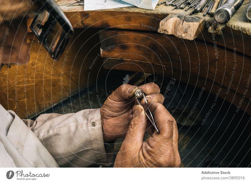 Jeweler working with diamond in workshop jeweler professional man goldsmith stone tweezers skill mature tool male master workbench jewelry small business