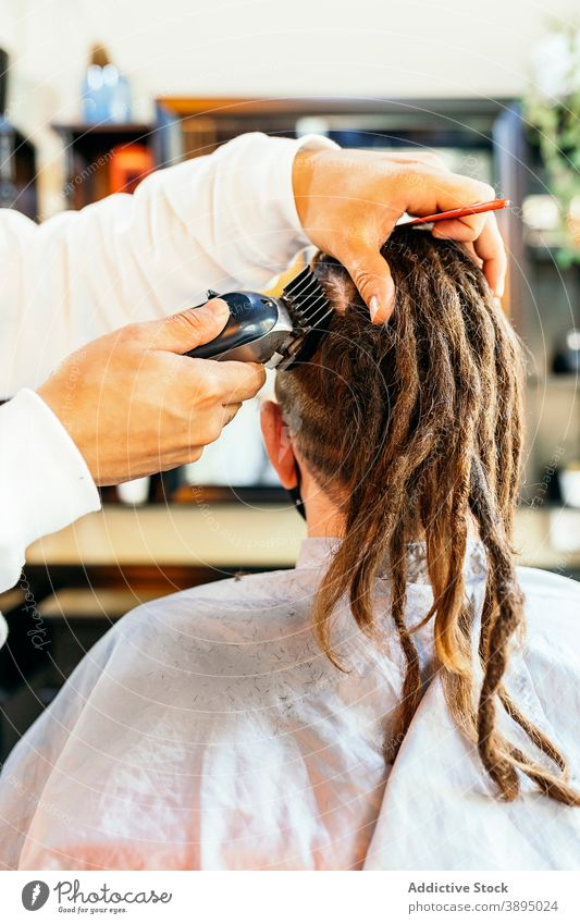 Crop barber trimming hair of client in salon barbershop grooming trimmer haircut men hairstyle hairdresser hairdo modern customer work hipster service busy guy