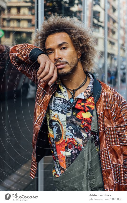 Stylish ethnic hipster man in trendy clothes style urban modern curly hair beard fashion young male african american black apparel lifestyle street handsome