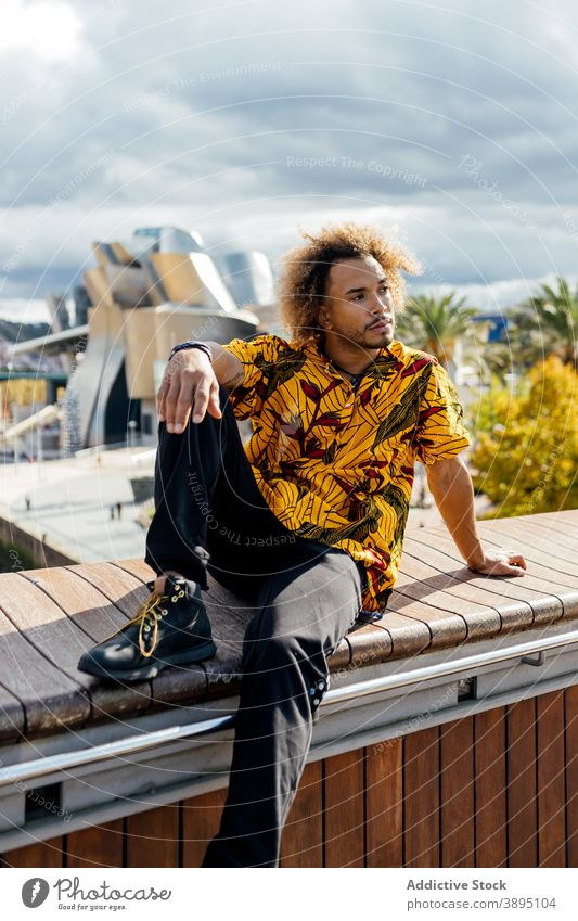 Confident trendy hipster man resting on street style informal fashion curly hair beard young modern colorful outfit guy african american black ethnic male