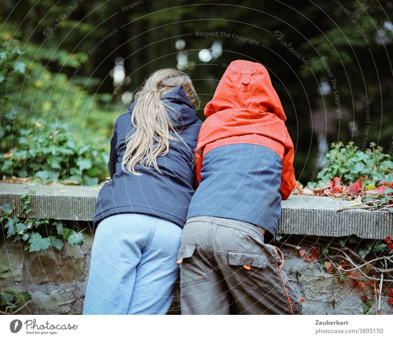 Two children in anoraks lean over a wall and look down Boy (child) Girl Anorak Rain jacket Stand Wall (barrier) Interest Trust Curiosity Red Blue Green mystery