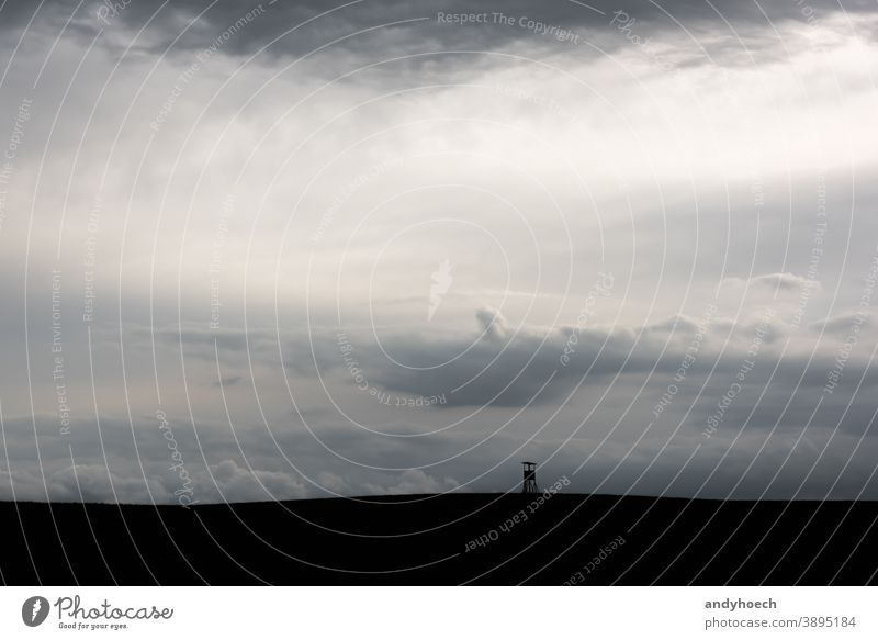 Silhouette of a high seat in thick clouds abstract Art Background beautiful black box stand cloudy copy space deer stand field frame game hide hideout hunt
