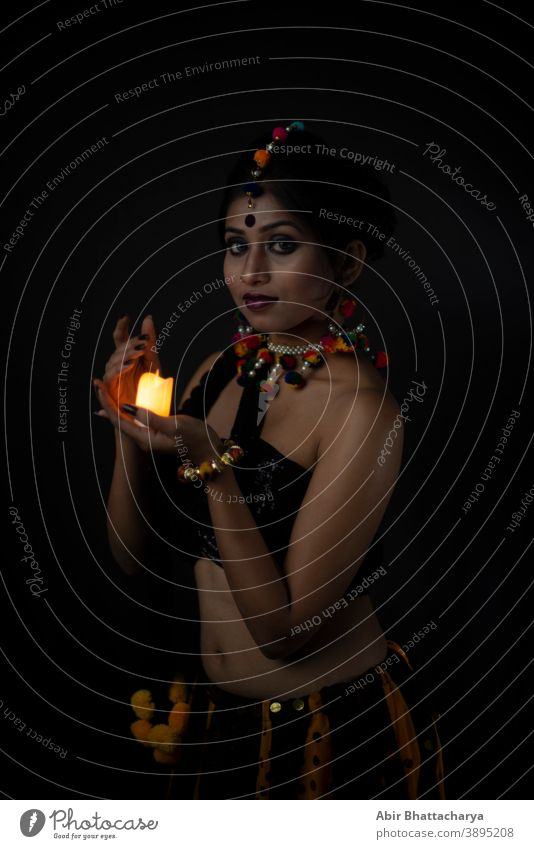 Portrait of Indian Bengali brunette woman in Indian traditional tribal/ villager dress and handmade ornaments with candle in dark copy space studio background. Indian lifestyle and fashion photography.