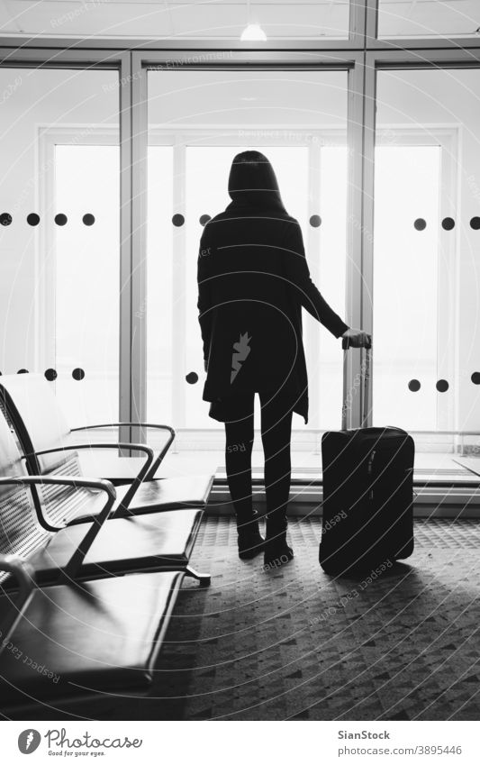 Young woman in the airport, looking through the window at planes travel b/w black white terminal flight airplane girl female luggage departure transportation