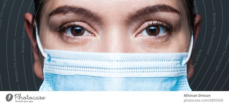 Young caucasian woman wearing blue surgical face mask closeup wide screen portrait coronavirus covid-19 female eyes doctor banner clinic disease epidemic fear