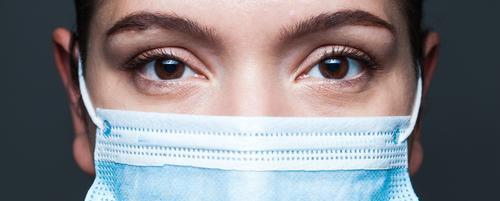 Young caucasian woman wearing blue surgical face mask closeup wide screen portrait coronavirus covid-19 female eyes doctor banner clinic disease epidemic fear