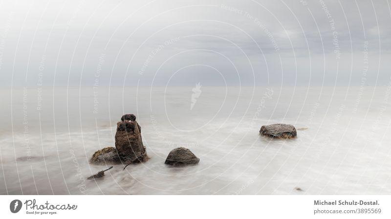 Three rocks in the calm waters of the Baltic Sea baltic Ocean sea Lake wave woge Water Sand Beach beach White white Blue blue Green green Sky sky cloud