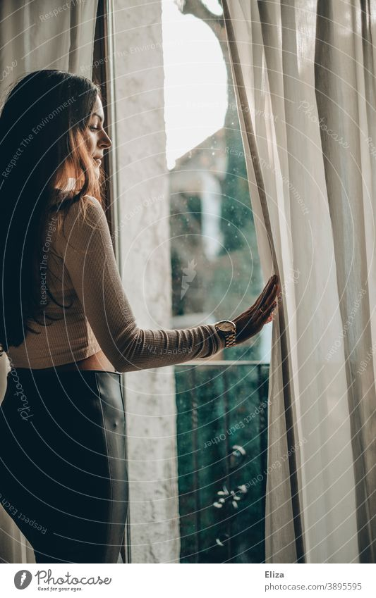 Young woman stands at the window and watches the // neighbourhood View from the window Woman Drape look out Window Window pane Longing stay at home Observe