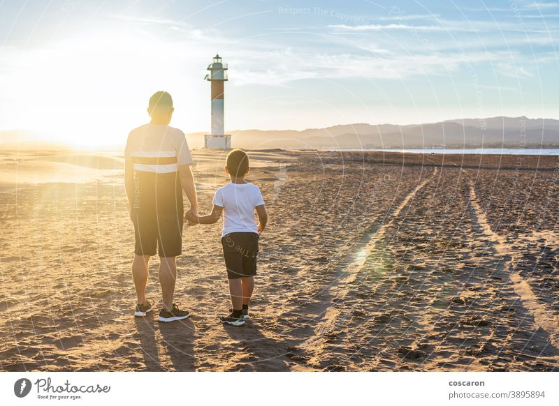 Grandfather and grandson looking a lighthouse on the beach at sunset back boy child childhood children coast dad day elderly family fangar far del fangar fun
