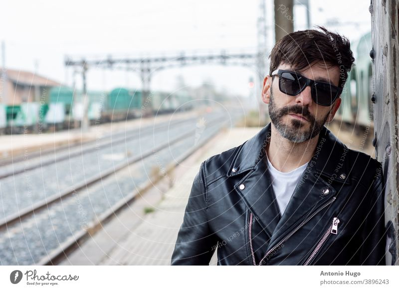 Portrait of a bearded Rocker with sunglasses on an abandoned train station portrait train car rock star rocker playing electric guitar tracks instrument music