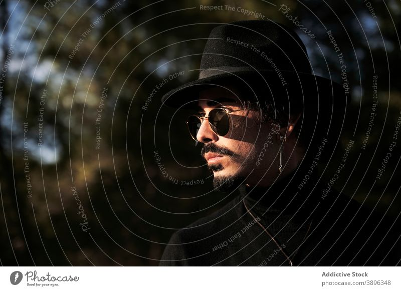 Stylish man in hat and sunglasses standing on meadow hipster style beard traveler piercing young male trendy modern handsome confident eyewear appearance