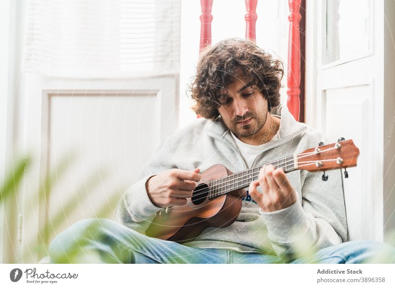 Pensive man playing ukulele guitar cheerful musician perform positive instrument young ethnic hispanic male melody home lifestyle song sound acoustic guitarist