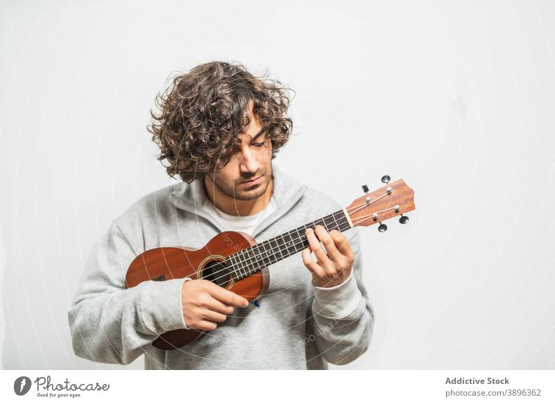 Cheerful man playing ukulele guitar cheerful musician perform positive instrument happy young ethnic hispanic male melody lifestyle song sound acoustic