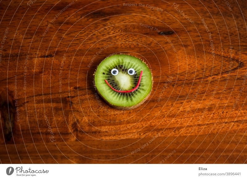 A slice of kiwi with a smiling face - Healthy nutrition Kiwifruit salubriously vitamins Face laughing Vitamin C Fruit Nutrition Vitamin-rich Fruity Funny