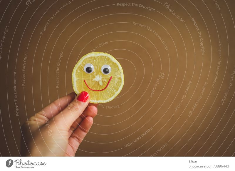 Sauer macht lustig - A hand holds a slice of lemon with a laughing face Lemon Funny Face Sour cheerful Slice of lemon vitamins salubriously Vitamin C Yellow