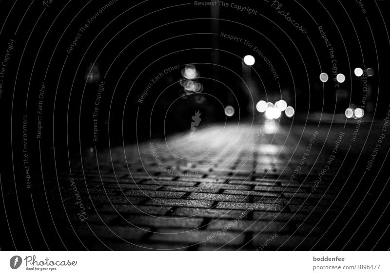 reflecting light of a street lamp on the paved sidewalk, in the background a bokeh of car lights and street lamps, focused on the foreground, frog's eye view
