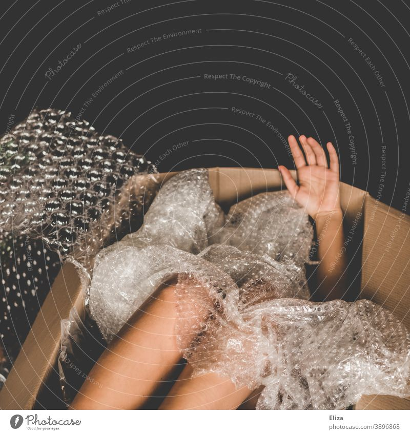 Man in a cardboard box, limbs peeking out between plastic packing material Cardboard Naked Package Shipping carton Human trafficking Packaging material