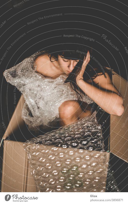 Woman sitting in a cardboard box between plastic packing material Cardboard Crate Human being Packaging Packaging material plastic foil Trash Plastic packaging