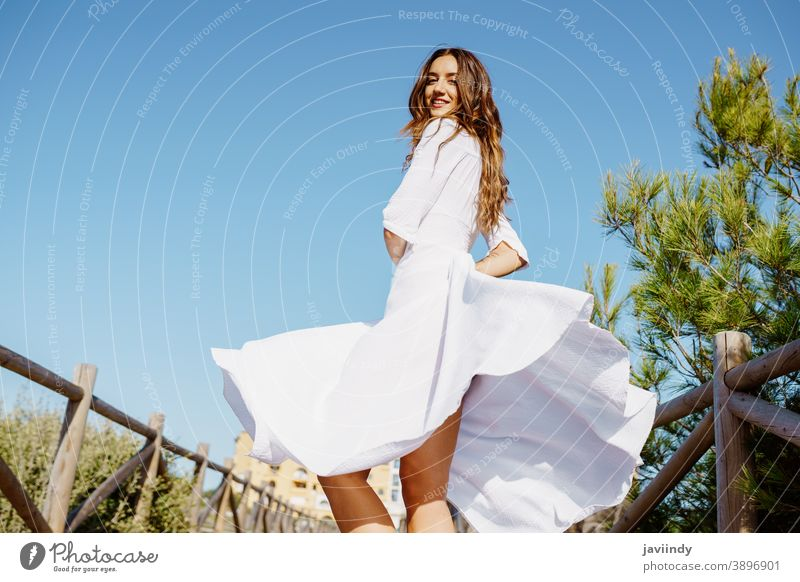 Young woman wearing a beautiful white dress enjoying a natural environment. girl wave fashion hair female extensions hairstyle fashionable model summer beauty