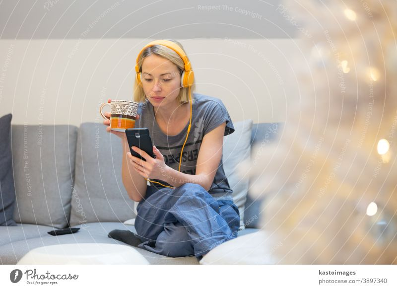Young cheerful woman sitting indoors at home living room sofa using social media on phone for video chatting and staying connected with her loved ones. Stay at home, social distancing lifestyle