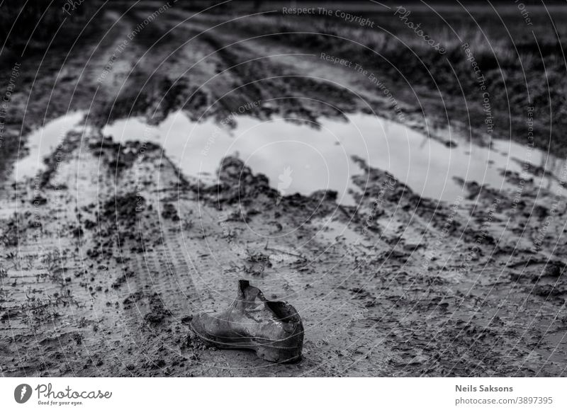 old rubber boot on dirt road. Splash and mud on road. offroad Rubber boots Boots Footwear Exterior shot Rain Wet Dirty Weather Bad weather Puddle Autumn