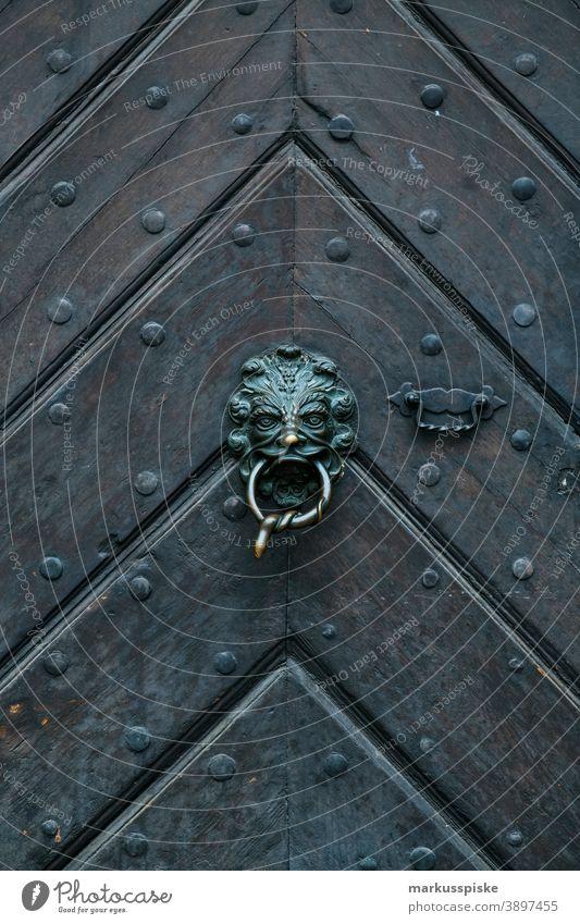 Old wooden entrance door with brass fittings Wooden entrance door Brass fittings Metal fitting motif Emblem Door opener vintage Retro Medieval times Herringbone