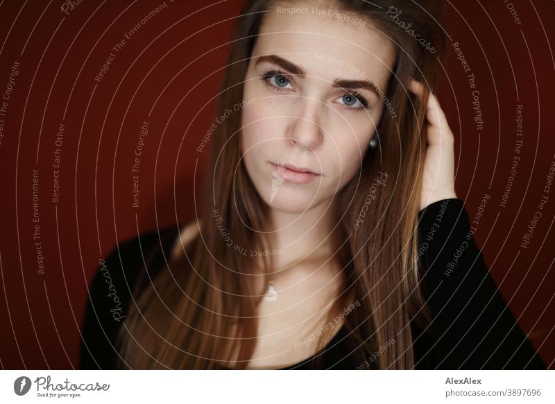Portrait of a young woman in a room with red wall Student daintily Jewellery Facial expression empathy Looking into the camera Copy Space left Close-up Emotions