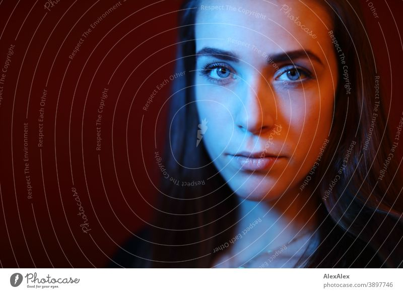 Portrait of a young woman in a room in front of a red wall with red and blue light Student daintily Facial expression empathy Looking into the camera