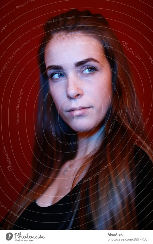 Portrait of a young woman in a room in front of a red wall with red and blue light Student daintily Jewellery Facial expression empathy Looking into the camera