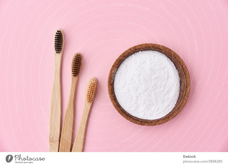 Three wooden bamboo toothbrushes and baking soda on pink background, top view care oral product natural hygiene organic nature dental teeth ecological health