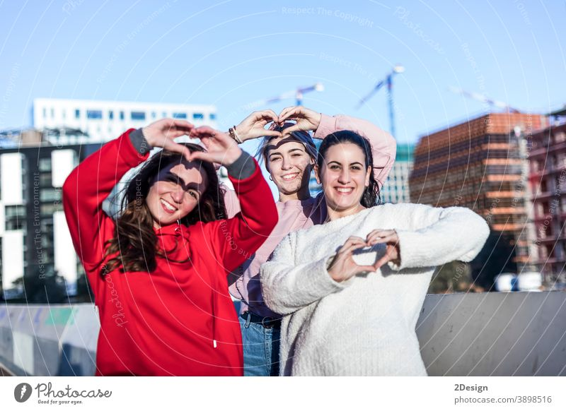 Portrait of three young woman showing finger gesture heart while smiling girl outdoor love female bonding closeness friendship gesturing flirting relationship