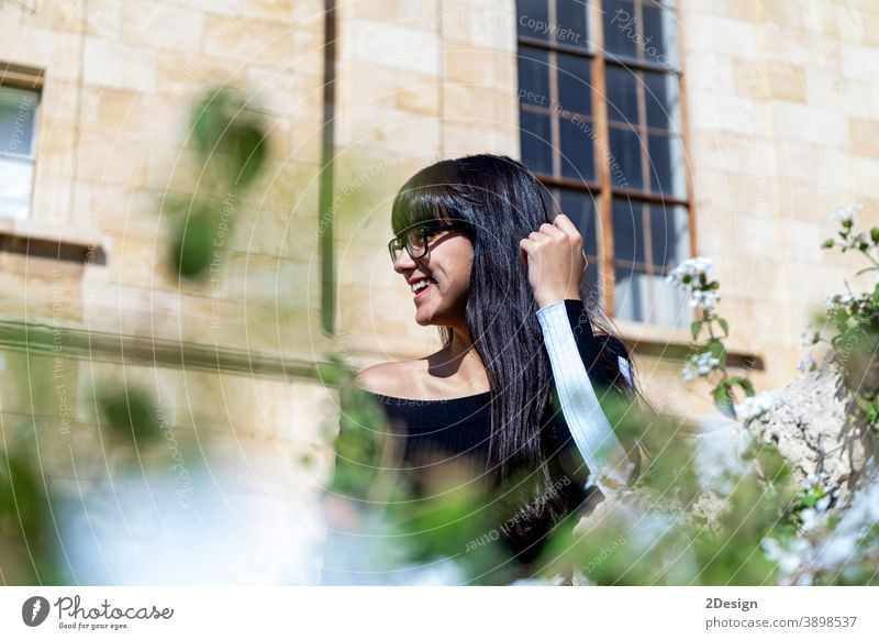 Portrait of beautiful young woman smiling while looking at camera standing in the street. outdoor person female lifestyle eyeglass happy girl portrait smile