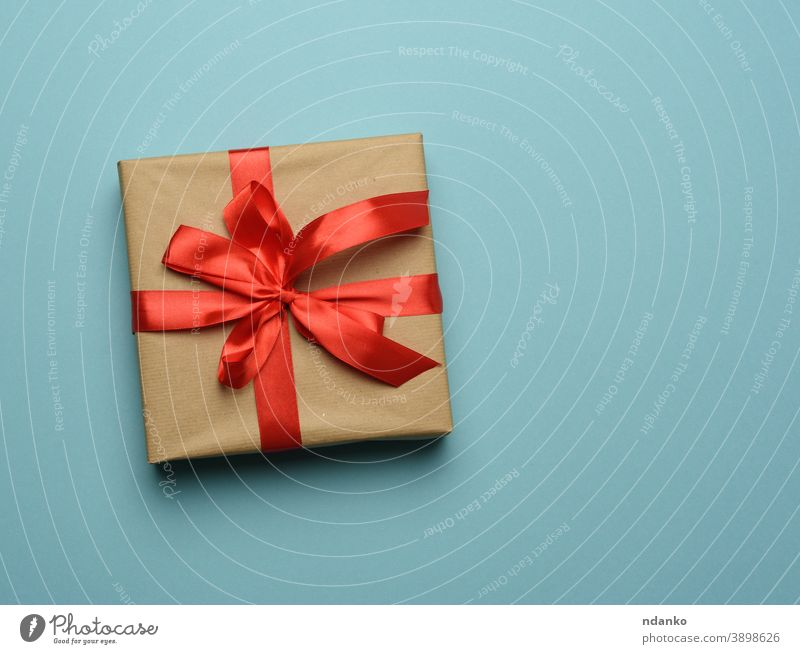 box wrapped in brown paper and tied with a red silk ribbon with a bow blue gift greeting holiday minimal new celebrate celebration anniversary backdrop