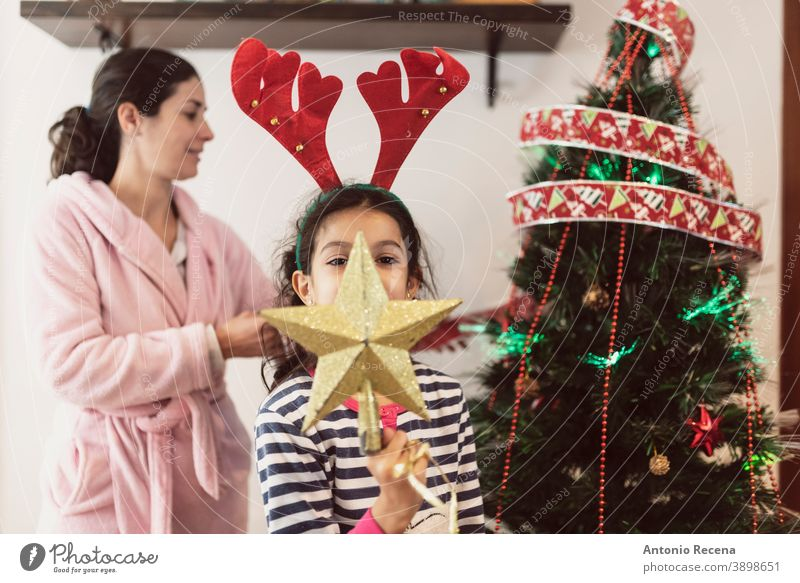 Mother and daughter in dressing gown and pajamas place Christmas decorations in realistic scene christmas tree children placing parties star illusion winter