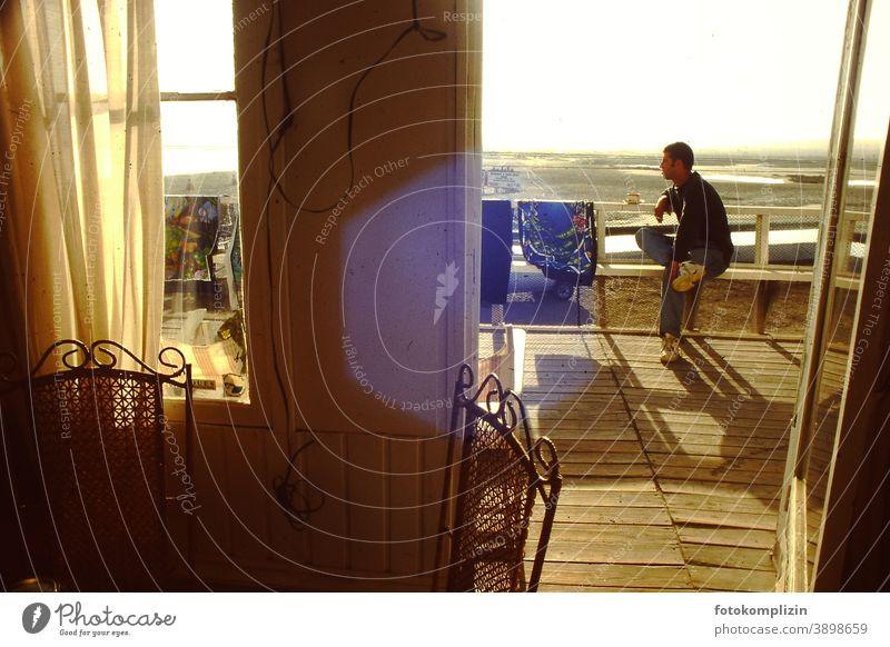 junger Mann sitzt auf einer Terasse und blickt in die Ferne beach holiday Fensteraussicht sitzen warten Balkon Strand Ferien Pause sommer ferien urlaub freizeit