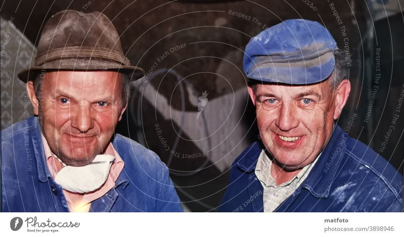 Two happy grandfathers at work. Blue overalls Cap Mask labour Hut