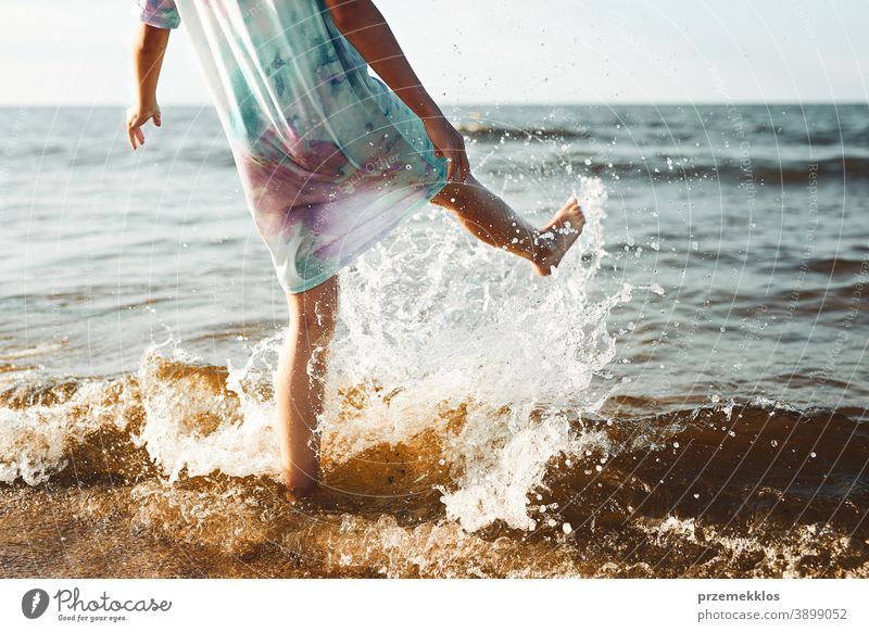 Girl spending a free time jumping splashing in a sea on a beach during summer vacation excited enjoy positive sunset emotion carefree nature outdoors travel