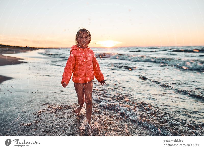 Playful little girl splashing a water towards camera enjoying a free time over sea on a sand beach at sunset excited positive emotion carefree nature outdoors
