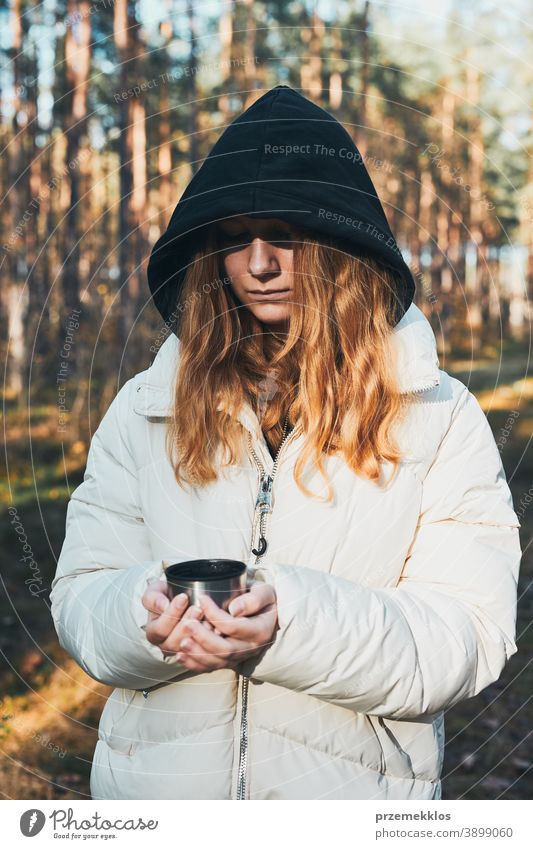 Woman in a hood having break during autumn trip holding cup with hot drink from thermos flask on autumn cold day active activity adventure coffee destination