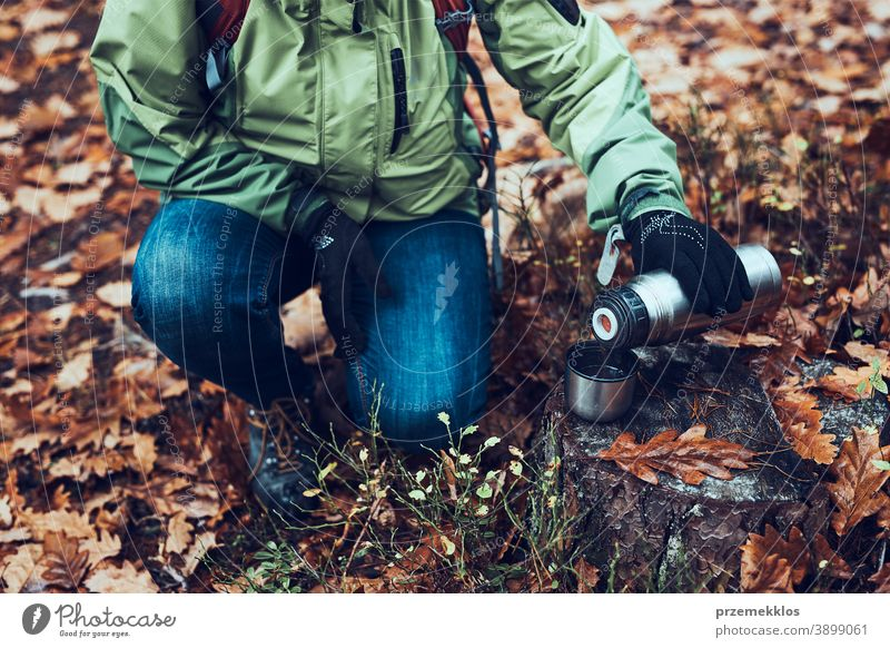 Woman with backpack having break during autumn trip on autumn cold day pouring a hot drink from thermos flask outdoors destination hiking holiday vacation hiker