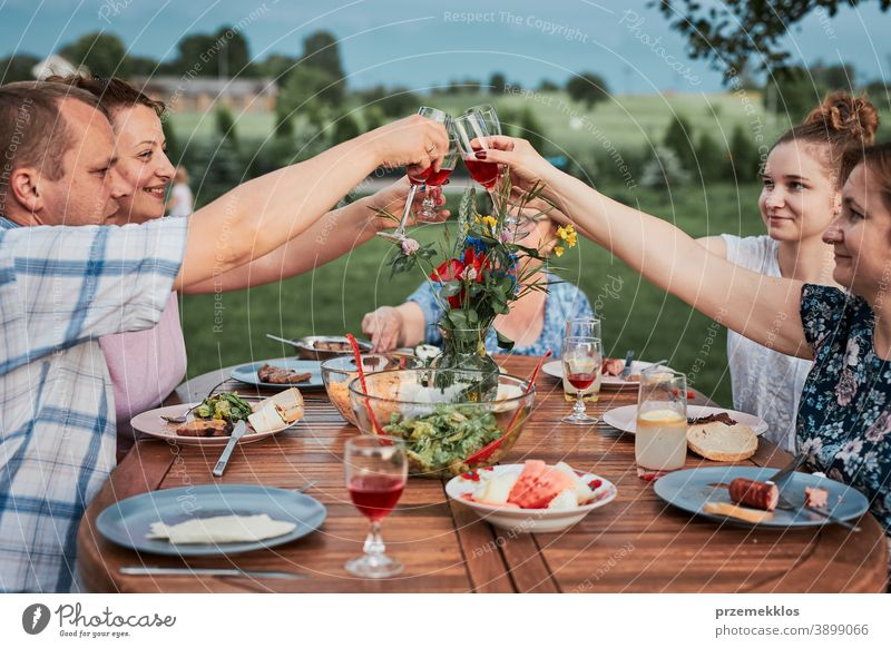 Family making toast during summer picnic outdoor dinner in a home garden feast having food man together woman child barbecue table eating gathering people