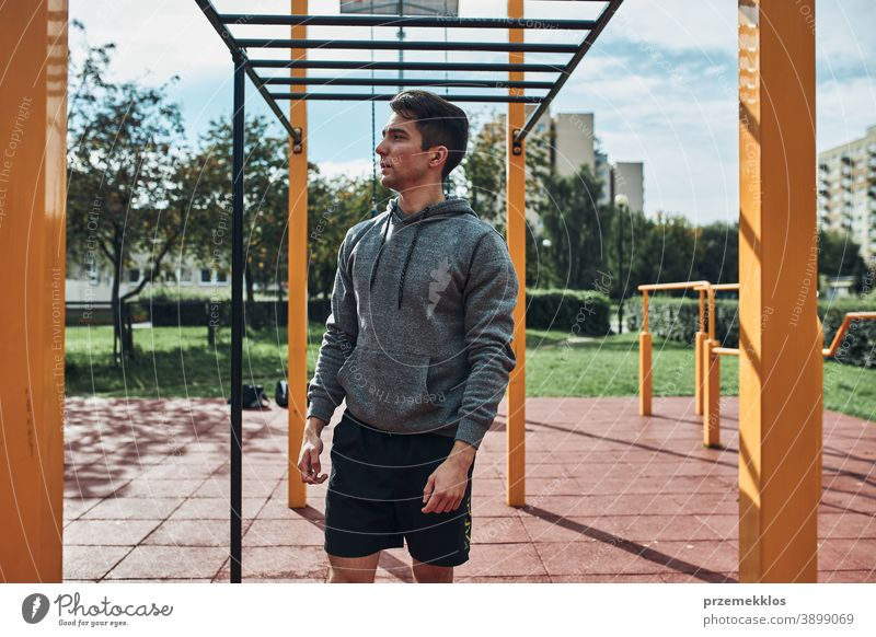 Young man bodybuilder having break during his workout in a modern calisthenics street workout park care caucasian health lifestyle male one outdoors person