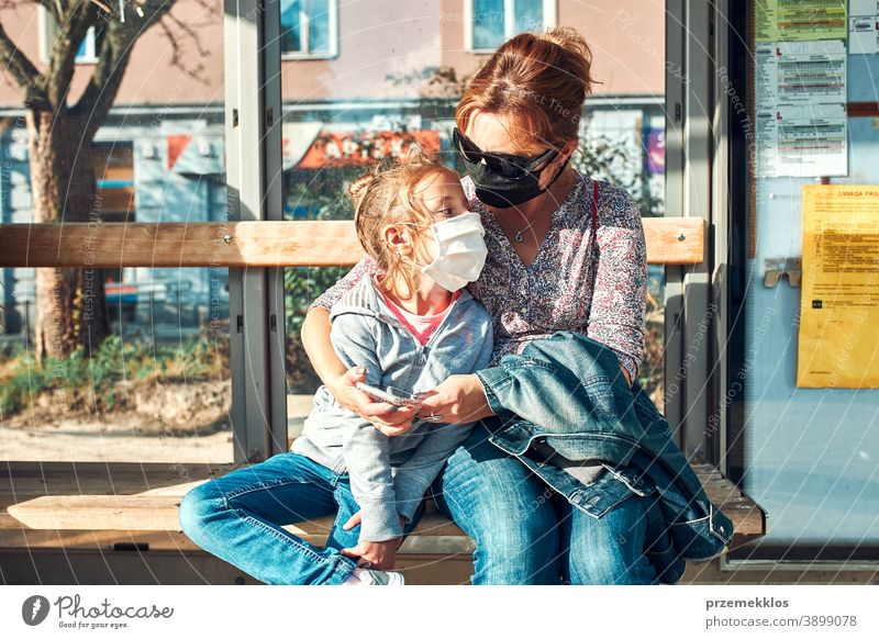 Woman and her child waiting for a bus sitting at bus stop of public transport woman mask face pandemic coronavirus outbreak protection girl parent daughter