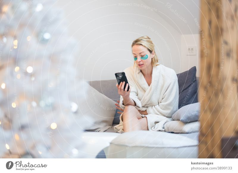 Young businesswoman wearing cosy warm bathrobe and cosmetic eye patches working remotly from home in winter Christmas time during 2020 corona virus pandemic. Work from home, selter in place, concept.
