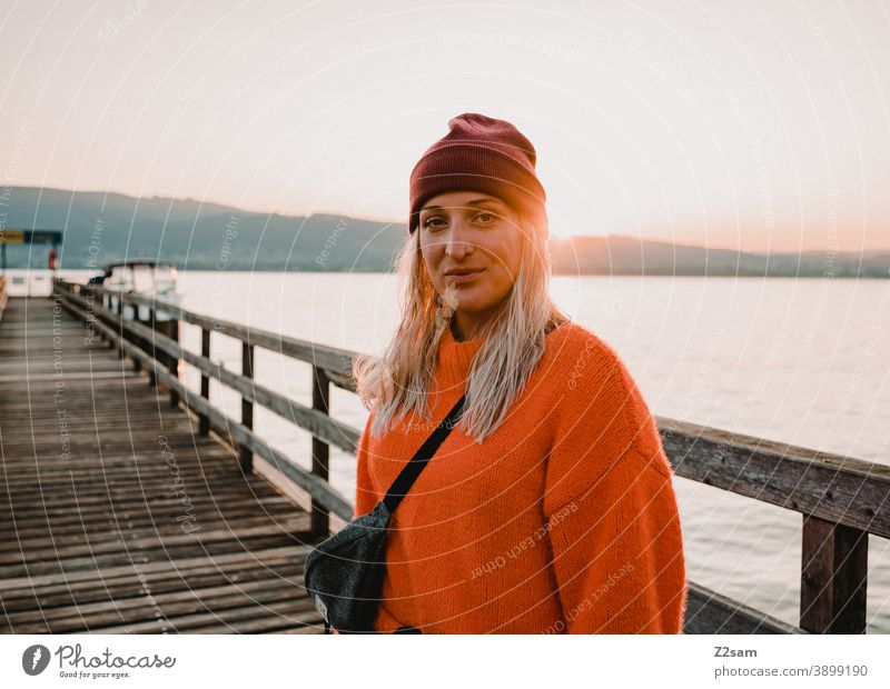 Young woman in the evening sun at lake Attersee Lake Attersee sunset Evening Sunset Nature Dusk Landscape Idyll Austria Footbridge Lakeside Exterior shot Orange