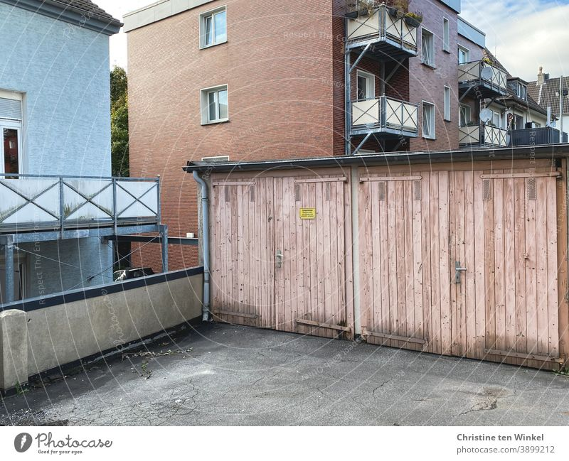Neighborhoods | backyard with a view of two old pink garage doors and the windows and balconies of the apartment buildings behind Backyard garages Garage door