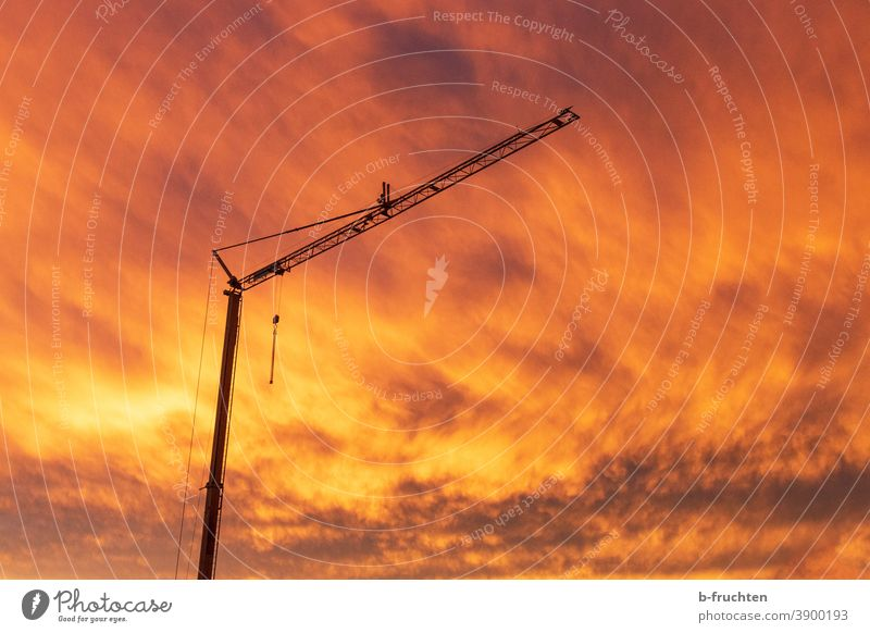 Construction crane in a fiery red cloud atmosphere Construction site Sky Clouds Exterior shot morning mood dawn Sunrise Silhouette Industry Crane